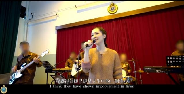 關心妍與壁屋懲教所青少年在囚人士組成的樂隊一起演奏和合唱。(政府新聞網短片截圖)