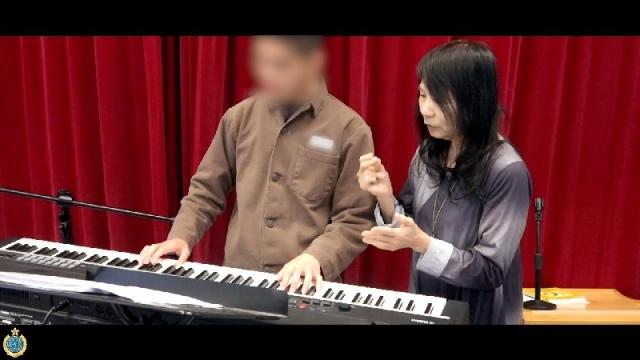 鋼琴演奏家羅乃新(右)在壁屋懲教所擔任樂隊導師已經十五年。(政府新聞網短片截圖)